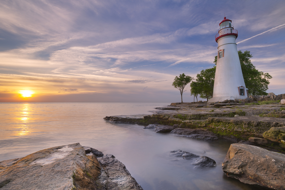 The Marblehead Lighthouse on the edge of a rocky shore at sunrise. There is fog on the water and moss growing on the rocky shore. the Lighthouse is painted white with red trim. There are a bunch of trees behind the lighthouse.