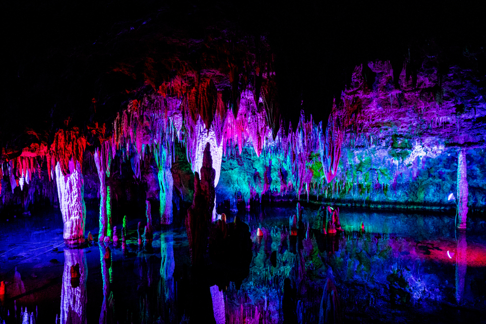 The interior of a large cavern system in Missouri. The stalagmites and stalactites are lit up using red, purple, green, pink, and blue lights. It looks like there is water at the bottom that is reflecting some of the lights further