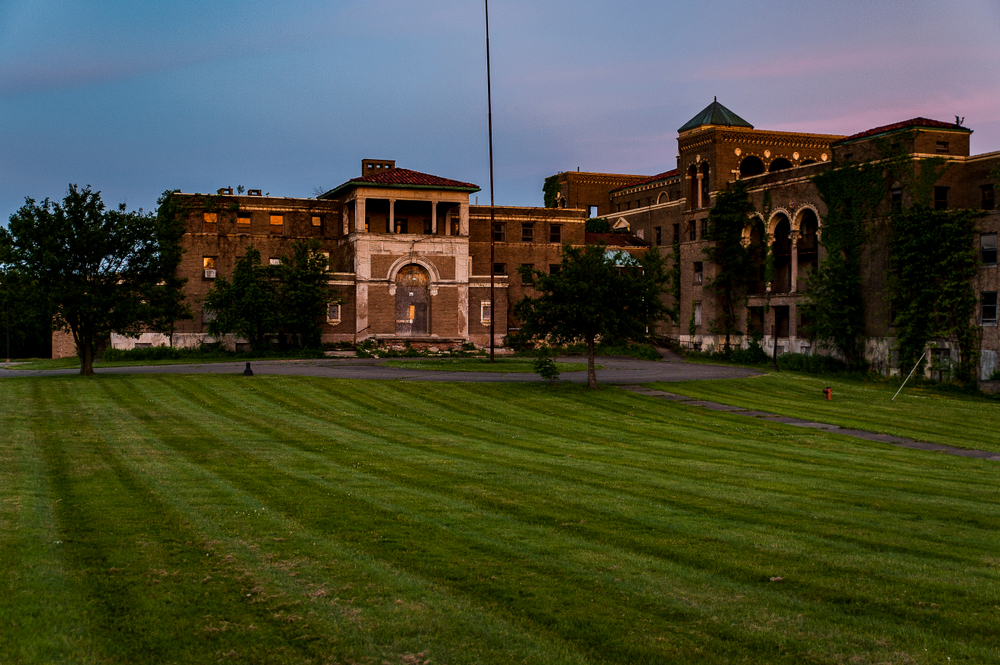 The abandoned Molly Stark Hospital. It is a massive building complex that is deteriorating. It is brick with white trimming. In front of the building is a freshly mowed lawn and trees. The photo is kind of dark because its twilight.