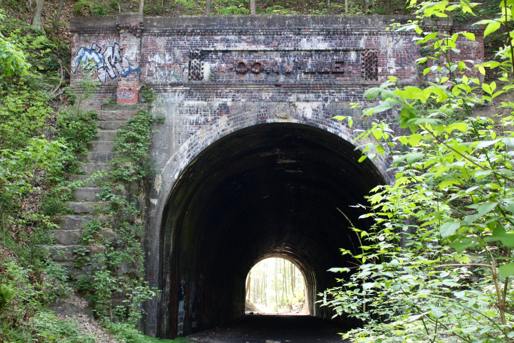 A supposedly haunted tunnel outside of Moonville Ohio. it is a stone tunnel that you can see through to the other side. Around the tunnel are wild trees, and there are vines growing on it. There is also scattered graffiti in white, blue, and black spray paint.