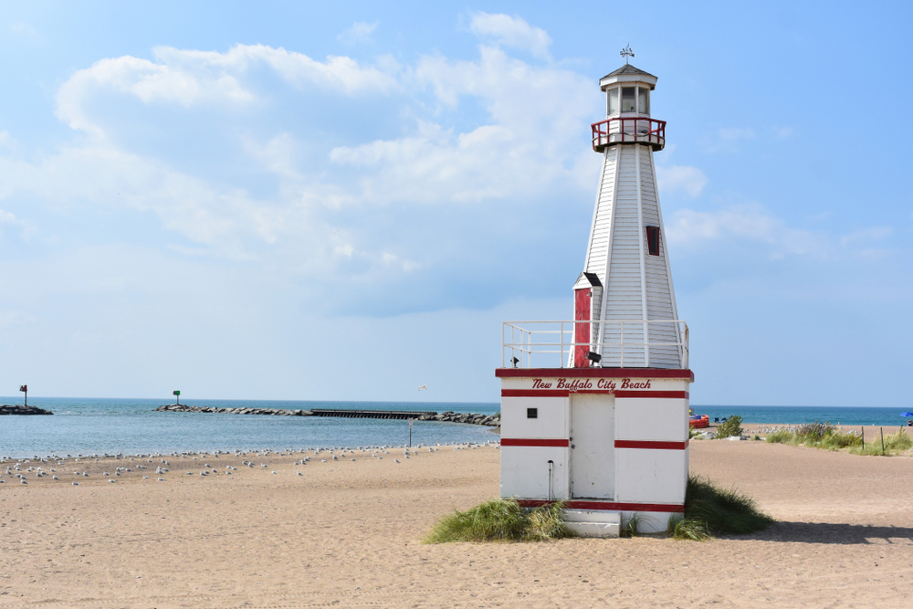 A small white and red lighthouse on the beach of New Buffalo Michigan. The lighthouse has 'New Buffalo City Beach' painted on it in red. The beach is sandy with some tufts of grass on it and there are seagulls near the water. It is a sunny day and one of the best stops on Michigan road trips.