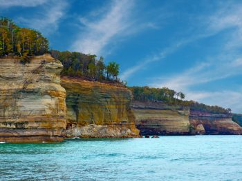 A view of the various cliffs at the Pictured Rocks National Lakeshore. The cliffs have layers of different colored rock, like yellow, green, and a rusty orange. There are trees on the rocks, most of them have green leaves but a few have orange leaves. It is a sunny day with a blue sky and the water looks very blue. Its one of the best stops on Michigan road trips