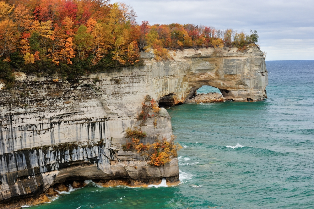 A view looking down the shore of the Pictured Rocks National Lakeshore. The rock formations look chalky and dry and white, cream, and grey in color. The water is very blue with small waves in the lake. On top of the rock formations there are lots of trees with yellow, orange, and red leaves. Some trees have no leaves or a some have green leaves. Its a beautiful view of Fall in Michigan
