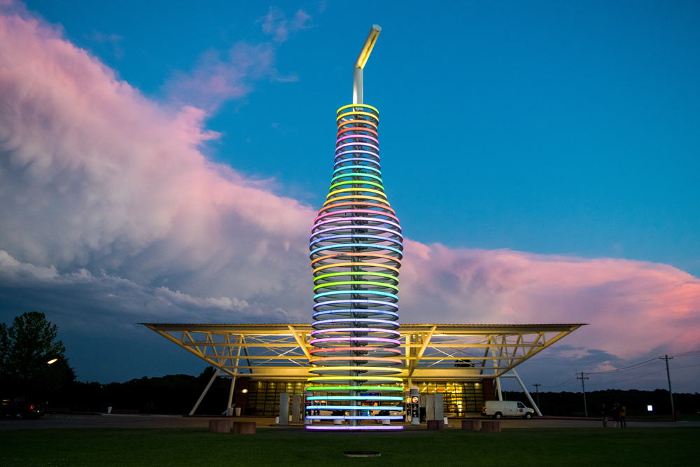 A large multi colored soda bottle. The bottle is colored with rings of lights. The lights are shades of yellow, orange, red, pink, purple, blue, and green. Behind the bottle there is a Mid Century style building with lights and windows and a van parked in front of it. It is sunset and there is a large swatch of pink and purple clouds in the background