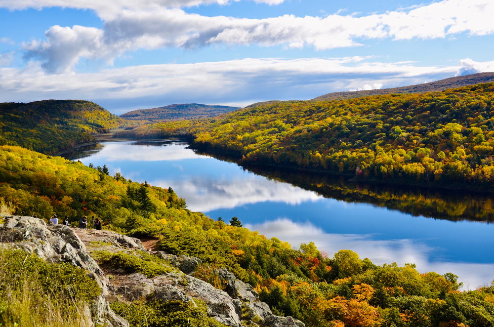 A large lake at the Porcupine Wilderness State Park. There are hills covered in trees and some of them have yellow and orange leaves. There are some rock formations that people are sitting on. The sunny partially cloudy sky is reflected in the lake.