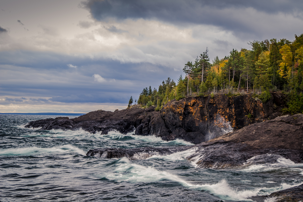The rocky shores of Presque Isle Park on a cloudy day. There are waves crashing against the rocky shore. The rock formations are dark brown with some having orange flecks in them. Just pass the rocky shore is a landscape of trees with mostly green leaves, but a few of the trees have yellow leaves.