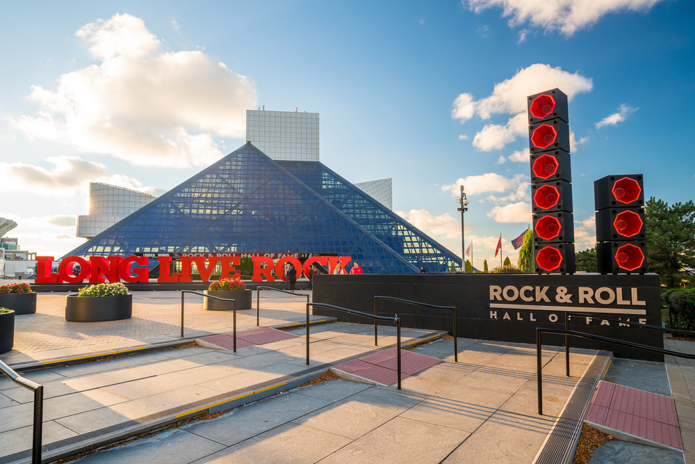 The exterior of the Rock and Roll Hall Of Fame. It is a large angular building with glass pyramids and square and round white tiled buildings. In front of the glass pyramids is a red sign that says 'long live rock' and there are structures that look like massive speakers that are black and red.