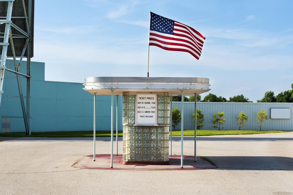 The ticket booth at a retro original route 66 drive in theater. It is made of glass bricks, has an overhang on all sides, and an American flag flying above it. It also has the ticket prices on the side on a white board with black lettering. In the background, you can see part of the drive in screen. One of the best route 66 attractions