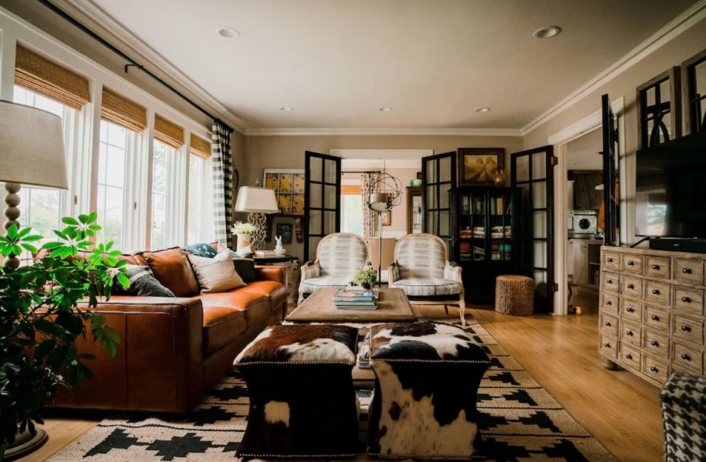 The cozy living room in a large historic home. It has a large brown leather sofa, two cowhide ottomans, and two accent chairs. There is a black and tan patterned rug, a tv on a bureau with lots of drawers, and plants. There are two sets of French doors on either side of the room that lead to other rooms in the house. Its one of the best airbnbs in the Midwest