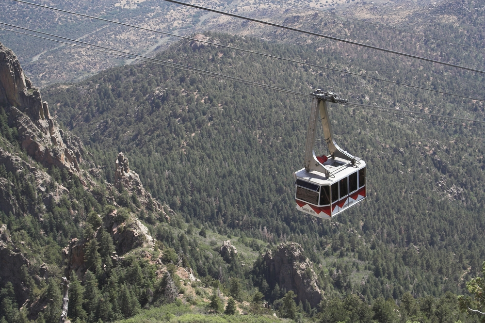 The Sandia Peak Tramway, which is a suspended shuttle over the side of the Sandia Peak Mountain in New Mexico. On the mountain there are trees and rocky cliffs Route 66 attractions.