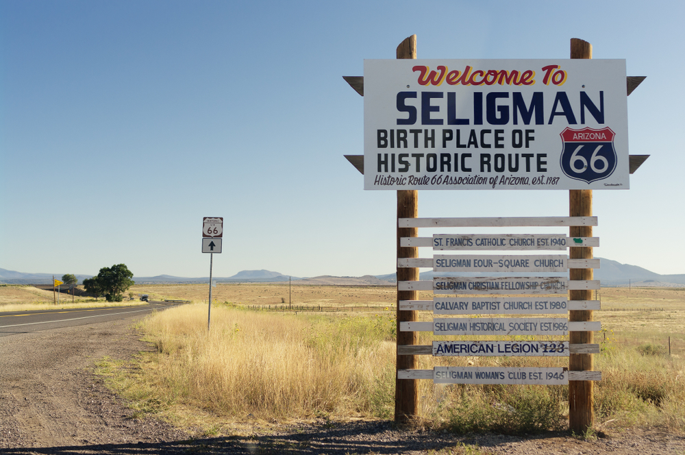 The Welcome sign when you enter Seligman Arizona. It is on the side of a road with tall grass around it and in the very far distance there are mountains. The sign has dark blue, yellow, and red lettering. Down the front it has information on each individual historic site in the town. One of the best route 66 roadside attractions
