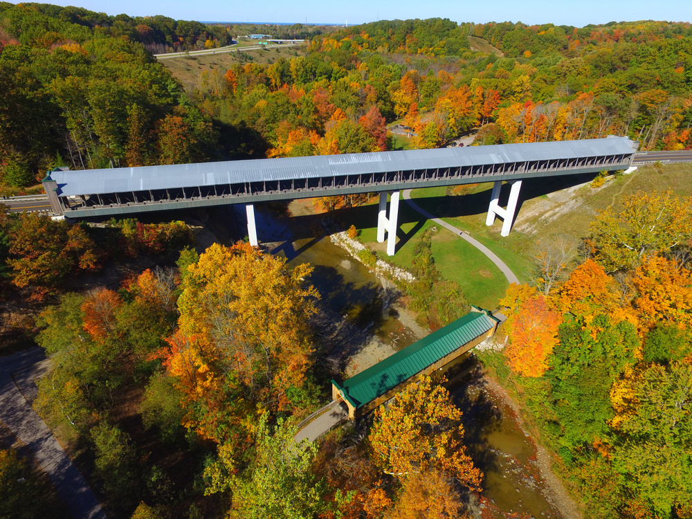 An aerial view of the Smolen-Gulf covered bridge, the longest covered bridge in the us. It has a metal roof and there is a smaller covered bridge slightly below it with a green roof. The bridges both cross the river. There are trees on each side with leaves changing colors that are green, yellow, orange, and red.