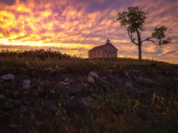 Sunset over the brick schoolhouse at Tallgrass Preserve with yellow flowers in the foreground.