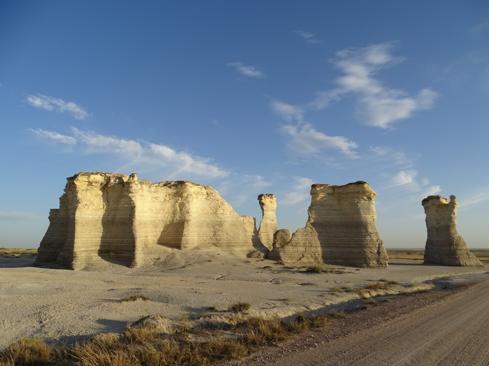 Large chalk rocks standing in a desolate landscape Monument Rocks is one of the things to do in Kansas