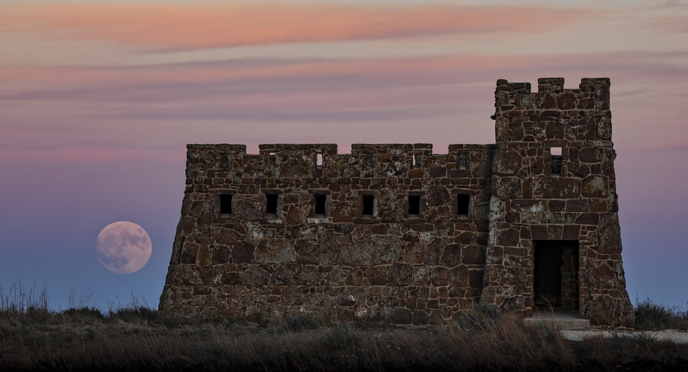 A castle with a hige moon and sunset in the background.