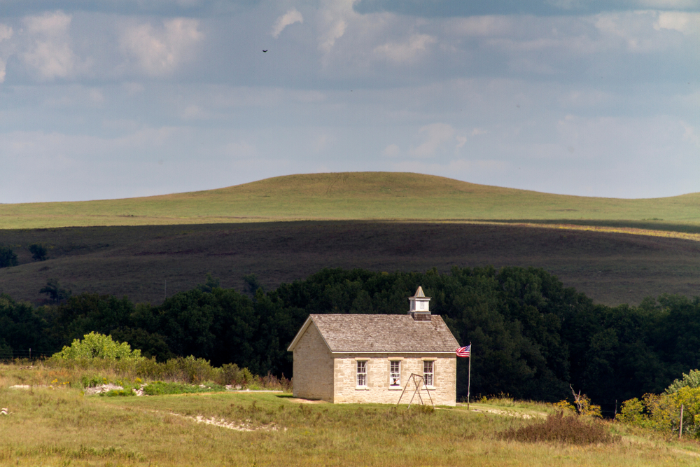 An old brick schoolhouse on the Tallgrass Prairie with hills in the background Things to do in Kansas