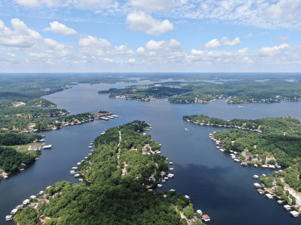 Drone view of large body of blue water with a lot of boats and homes along its fingers. things to do in Missouri.