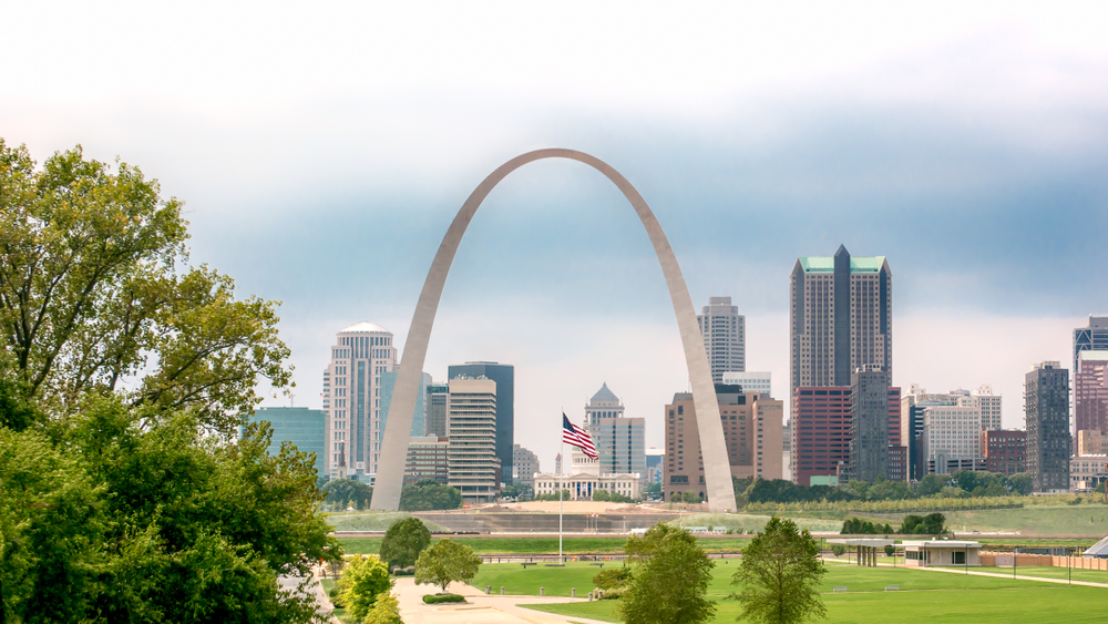 Large arch with city skyscrapers in background and American flag in foreground.