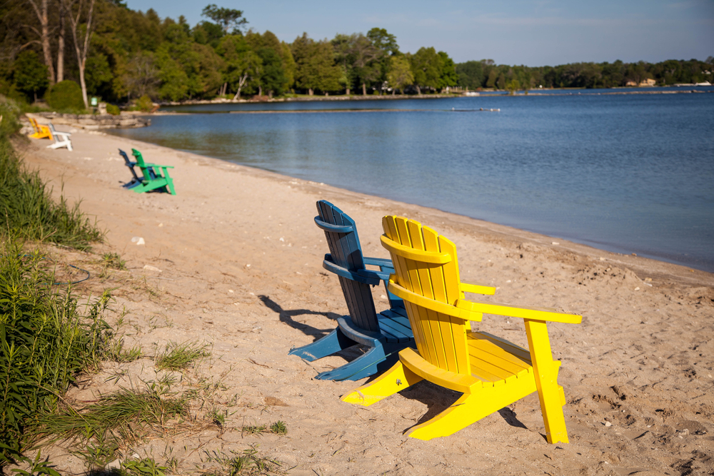 Empty chairs on a beach with trees in the background in an article about things to do in Door County
