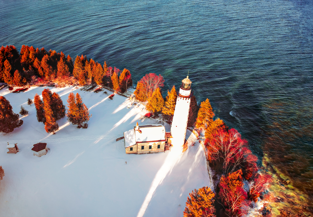 A island with fall foliage and a lighthouse all covered in snow.