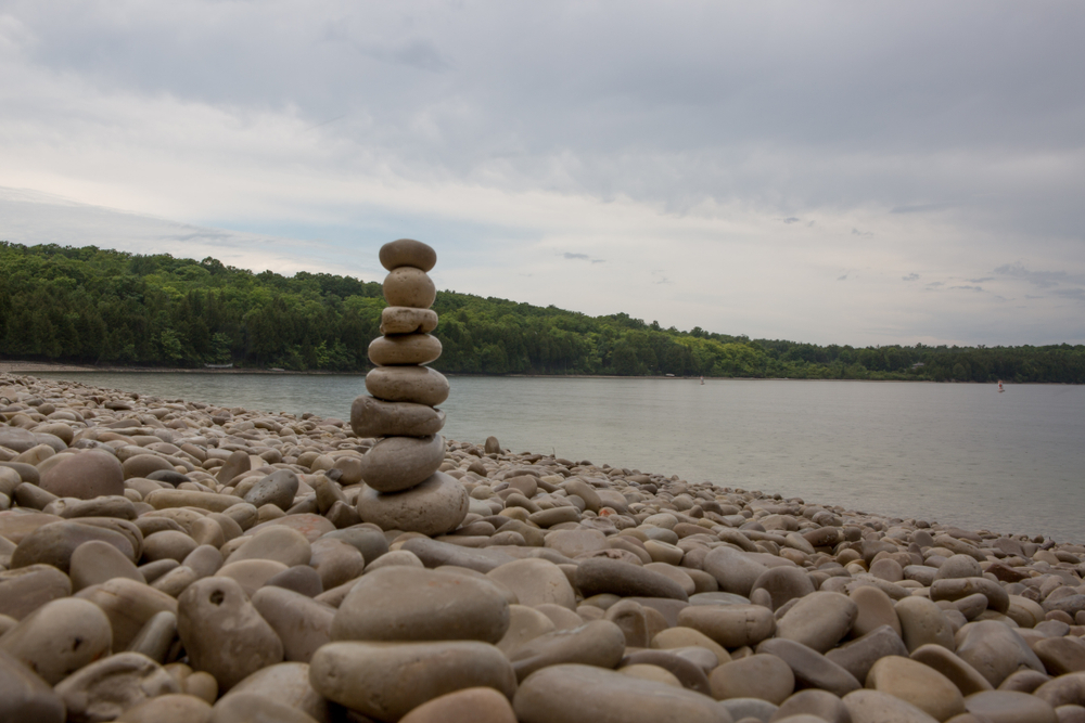 Pebbles piled up on a beach with trees in the background in an article about things to do in Door County