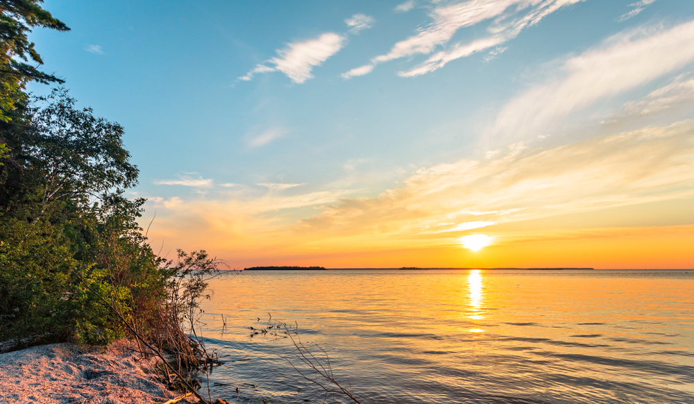 Sunset from a beach with trees in the foreground in an article about things to do in Door County