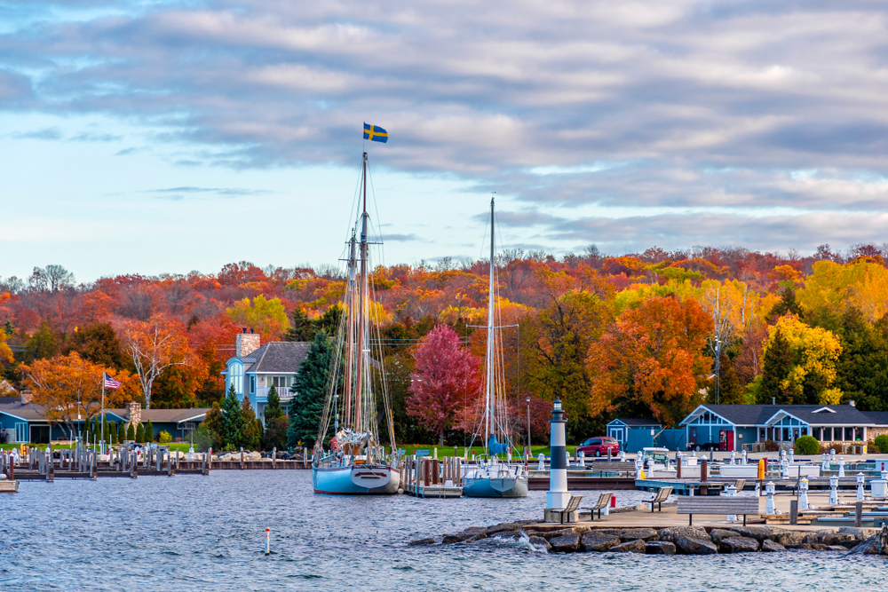 A waterfront town with a hrabout and beautiful fall foliage in the background.