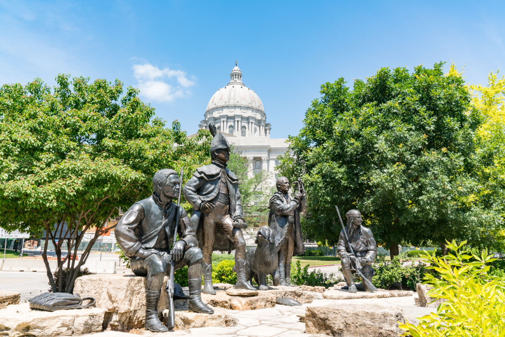 Bronze monument of 4 men and 1 dog on standing on stones with capital building in background. Things to do in Missouri/
