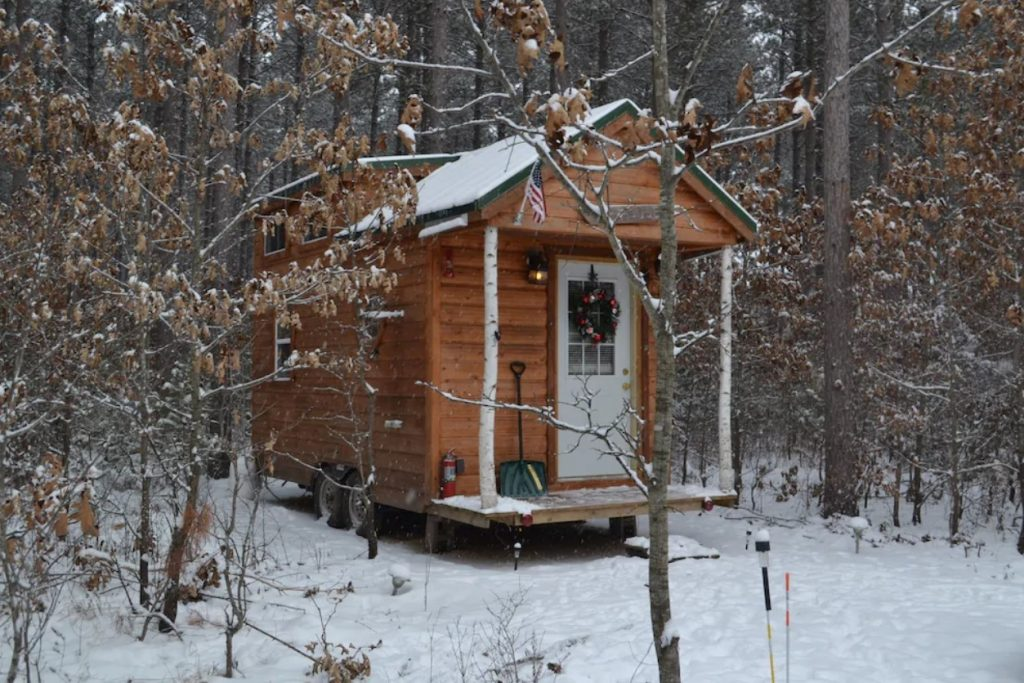 The exterior of a tiny cabin in the woods of Wisconsin. The front of the cabin has birch wood pillars, a white front door, and a small front porch. The woods are covered in snow. Its one of the best airbnbs in the Midwest