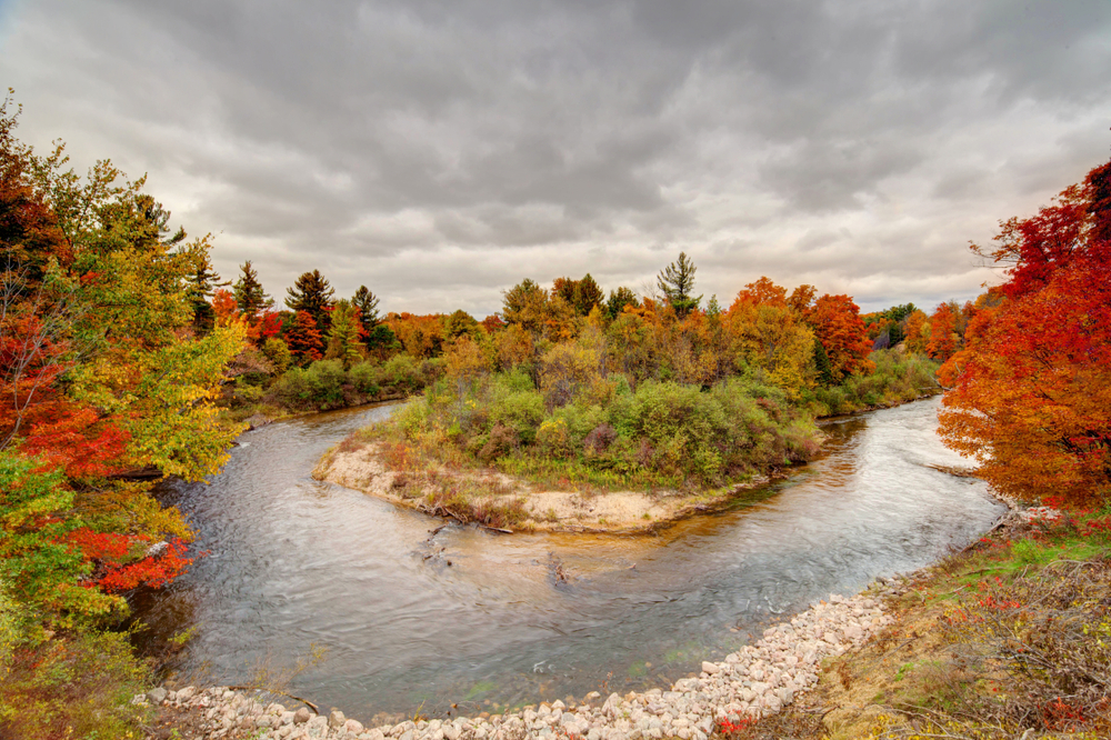 The view of a bend in the river near Traverse City Michigan. The river bank is covered in trees and rocks. The trees have red, orange, and some yellow leaves. There are also shrubs that still have green leaves on them.