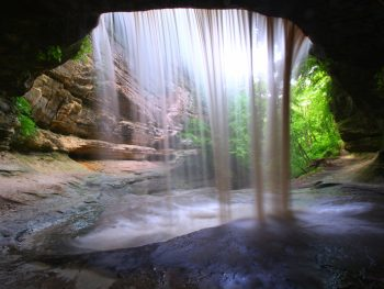 A cave with a waterfall flowing over the side and lush green trees behind. In an article about waterfalls in Illinois