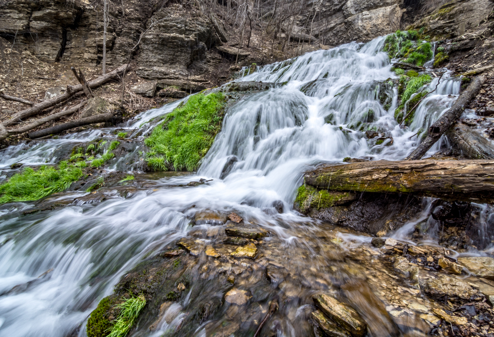 Waterfall cascading over rock formation with some green moss growing and brown logs.
