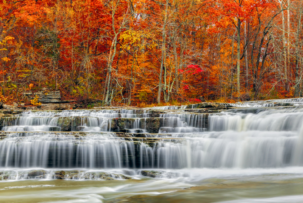 Cascading waterfalls over rock formations flow down to river below with bright red, orange, and orange atumnal trees in background. Beautiful waterfalls in the midwest