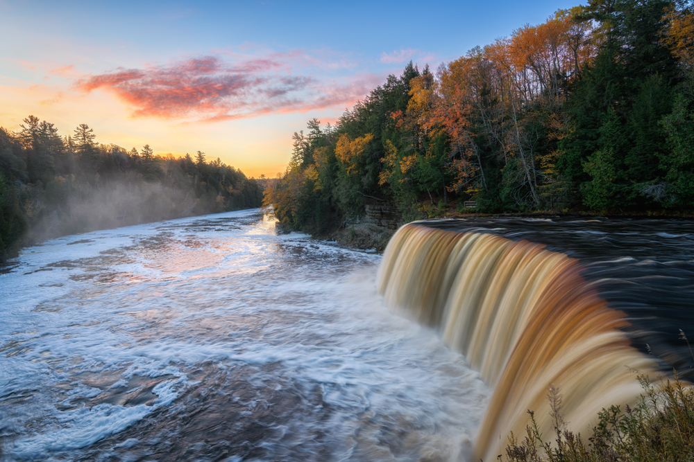 Brownish water flowing over rocks into flowing river below. Trees on both sides of river. Waterfalls in the Midwest.