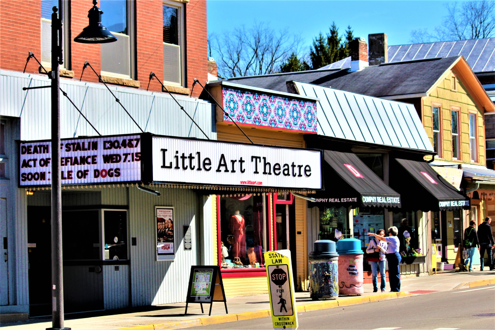 The charming streets of Yellow Springs Ohio. The photo centers on the Little Art Theater and two other shops. The theater is painted light blue-ish gray and has a simple marque in front of it.