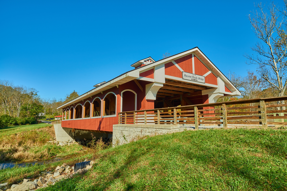 A barn-like covered bridge spans a creek with grassy banks in Hueston Woods state park, one of the best state parks in Ohio.