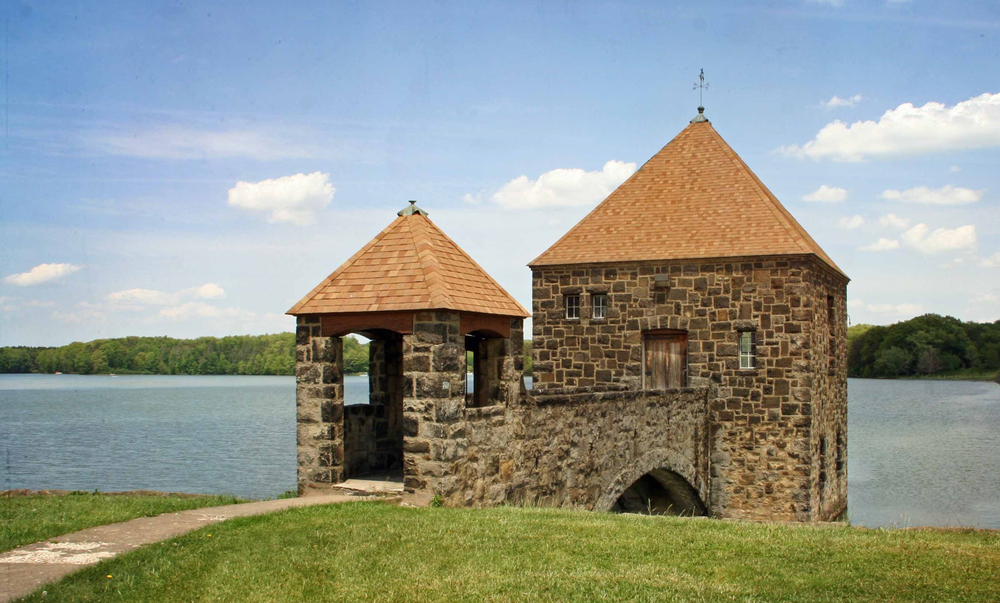 Brown stone structure with light brown pointed roofs with ornate arch leading to wooden front door, with lake in background.