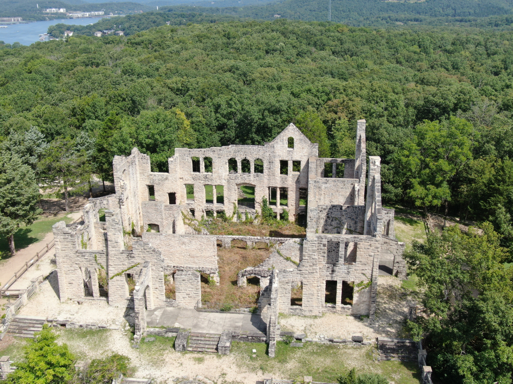 Ruins of white-brick castle surrounded by green trees. things to do in Missouri.
