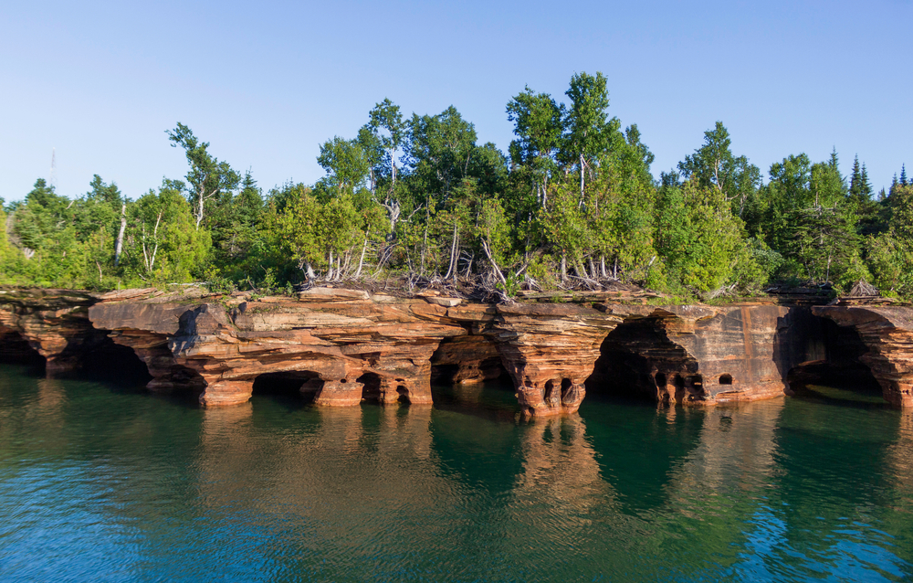 The unique rocky shore of the Apostle Island National Lakeshore. The shore has trees growing on it with green leaves. One of the most unique places for a Wisconsin weekend getaway.