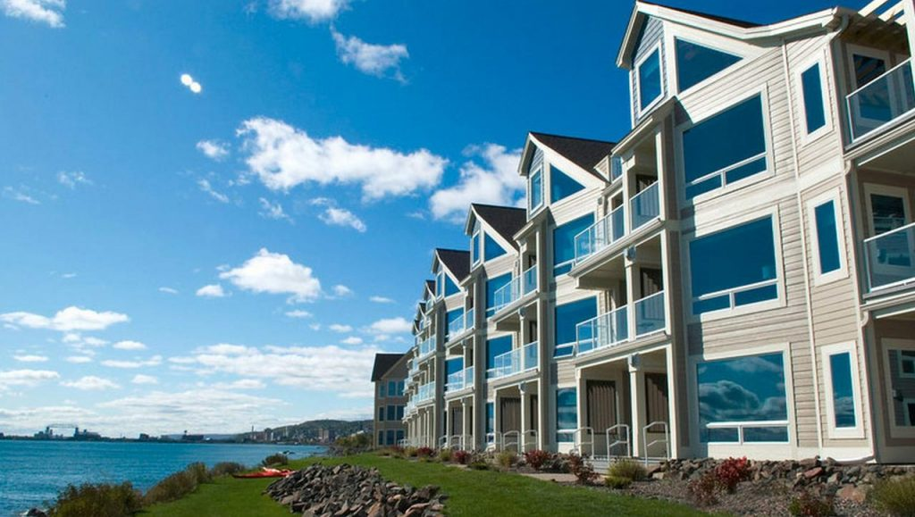 The exterior of a luxury resort on Lake Superior. There are lots of windows and small balconies on the resort. It is on a grassy shore of the lake with views of the city of Duluth in the distance.