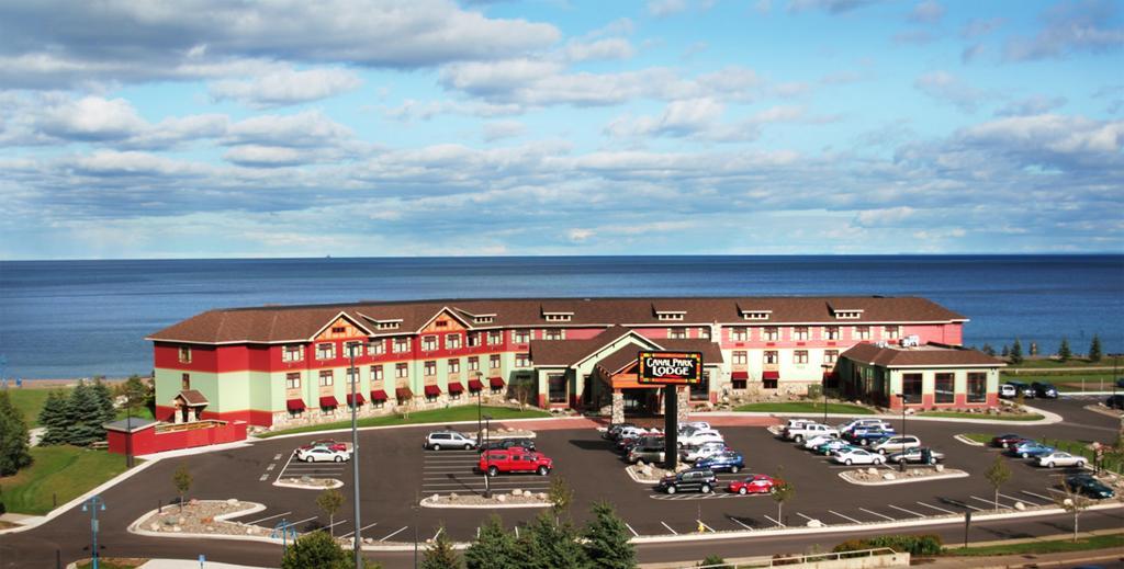 An aerial view of a retro style resort in Minnesota. It is mint green and red and has lots of windows. In front of it is a large parking area. Behind it you can see Lake Superior for miles in the distance.