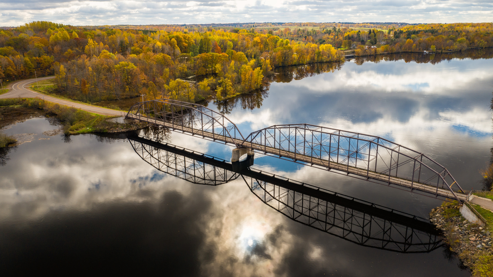 A bridge going over the Mississippi River to a shore of the river covered in trees. The trees have yellow, orange, and some green leaves. You can see clouds reflected in the water of the river.