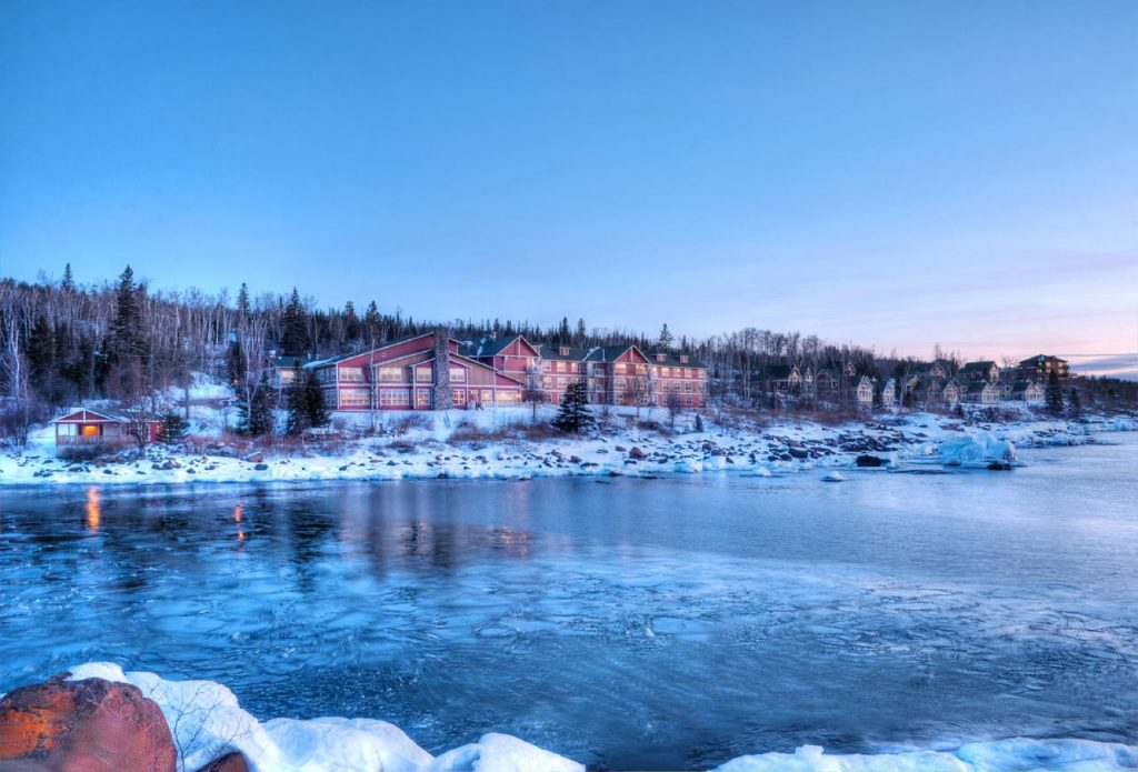 The view of a resort in Minnesota on Lake Superior. You can see the resort all lit up across the frozen lake. There is snow on the ground and it is twilight.