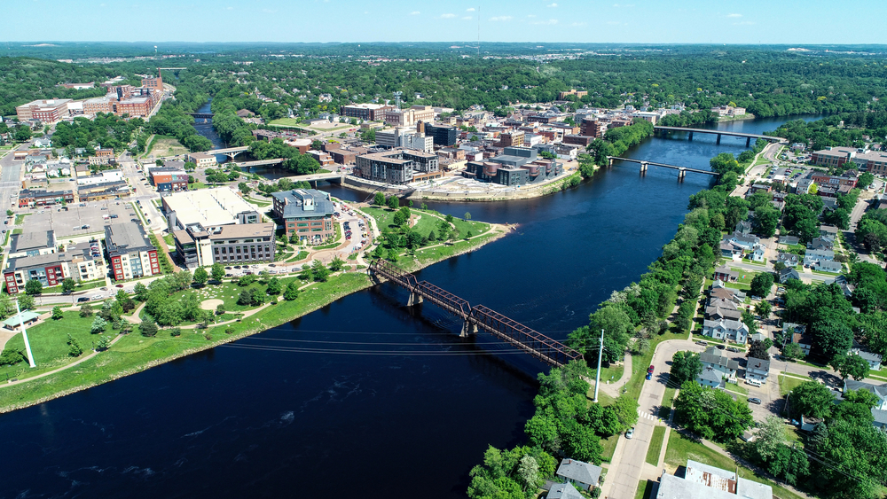 An aerial view of the college town Eau Claire, a town on the edge of the Mississippi River. There are lots of tall buildings and homes surrounded by trees.