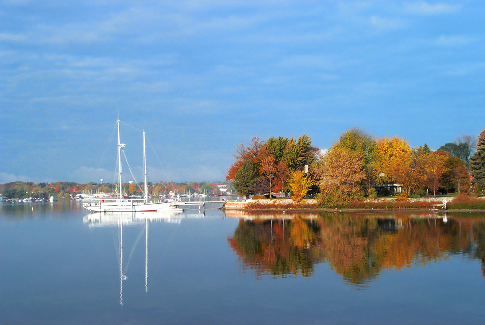 Sturgeon Bay with a boat on and fall colors on the island