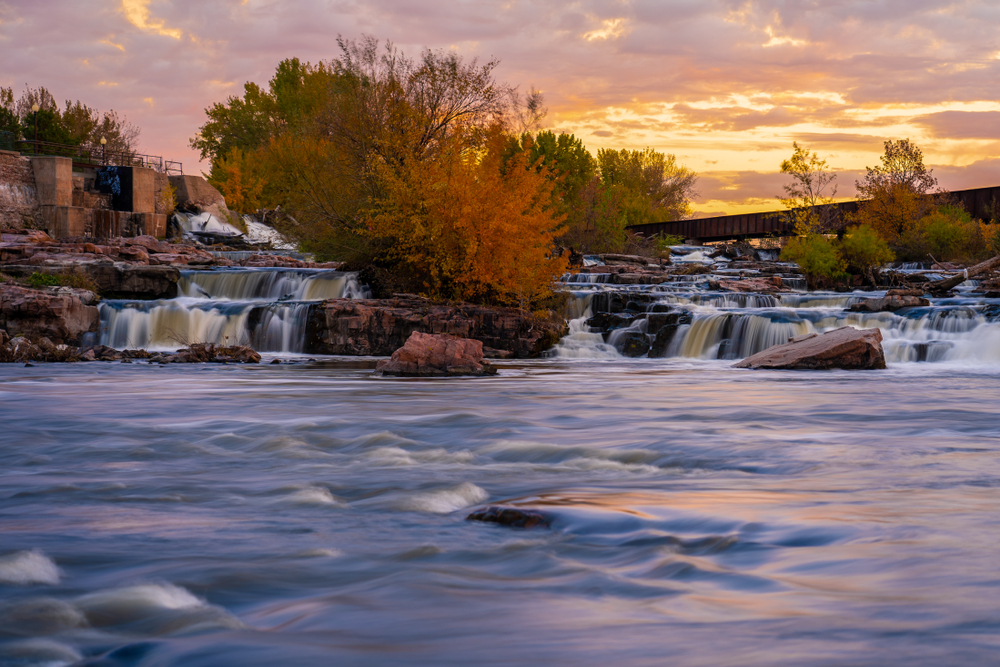 fall  in south dakota on display with waterfalls, orange leaves on trees in autumn and orange sunset in background.