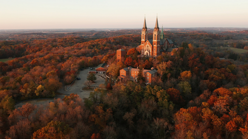 A church on a hill surrounded by beautiful fall colors in an article about Fall in Wisconsin