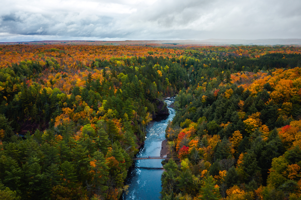 A Aerial View of a fall tree canopy with a river running through in an article about Fall in Wisconsin