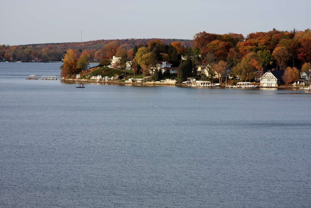 A Lake with white houses around and trees with fall colors a perfect place for Fall in Wisconsin