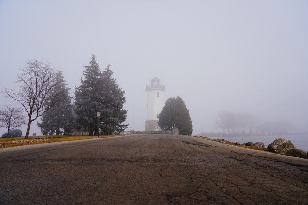 A lighthouse in the mist surrounded by trees in an article about fall in Wisconsin